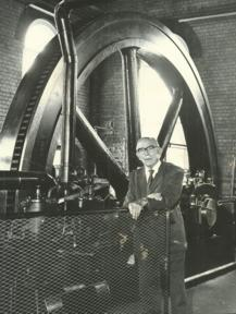 Harry Cusworth Standing Next to the Flywheel of the Hathorn Davey Steam Engine
